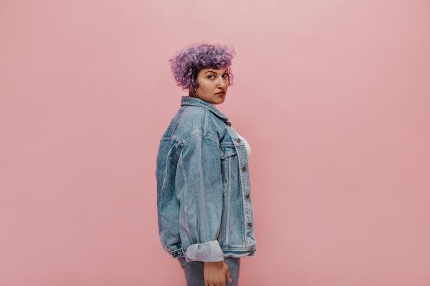 Krótkowłosa dorosła piękna pani o poważnym wyglądzie w stylowej kurtce jeansowej oversize i spodniach na różowo na białym tle.
