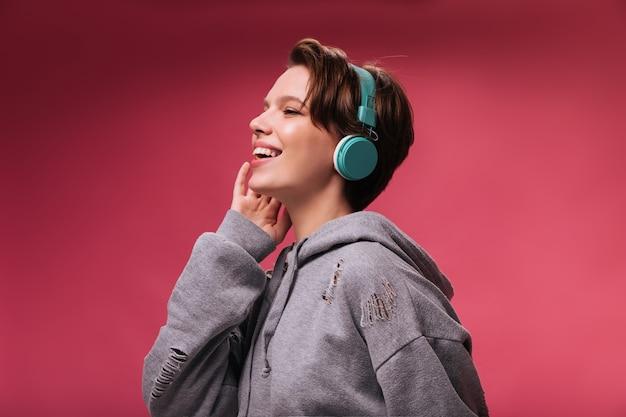 Krótkowłosa dziewczyna w dobrym nastroju, słuchając piosenki w słuchawkach. wesoła kobieta w szarej bluzie z kapturem uśmiecha się i lubi muzykę na różowym tle na białym tle
