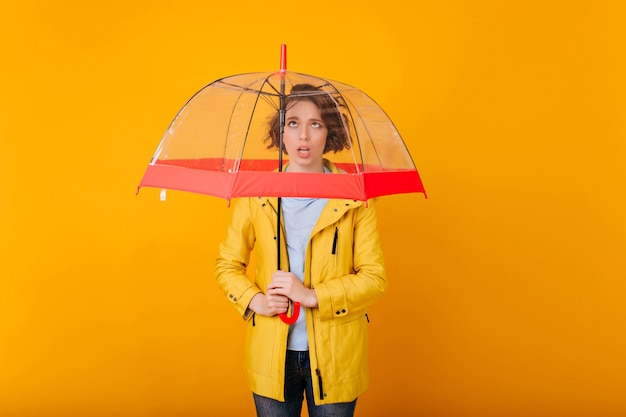 Krótkowłosa dziewczyna wyrażająca smutne emocje podczas sesji zdjęciowej z parasolką. modelka z parasolem przygotowuje się do deszczowej pogody.