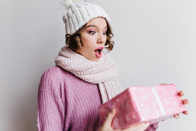 Krótkowłosa europejska dziewczyna w kapeluszu, pozowanie emocjonalnie, patrząc na prezent na nowy rok. wewnątrz zdjęcie zdumionej młodej damy w uroczym szaliku trzymającej różowy prezent.