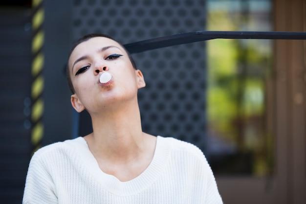 Krótkowłosa kobieta guma do żucia i patrząc na kamery