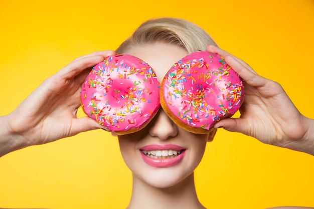 Krótkowłosa modelka zakrywająca oczy za dwoma różowymi pączkami