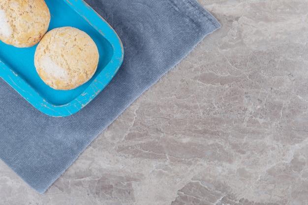 Kruche ciasteczka na niebieskim talerzu na kawałku materiału na marmurze