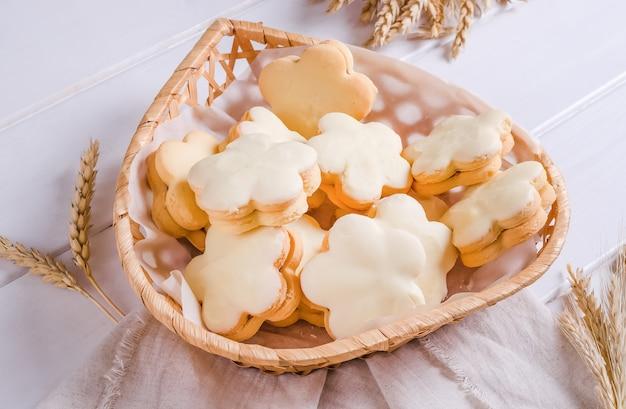 Kruche ciasteczka pokryte białą glazurą w wiklinowym koszu na białym drewnianym tle