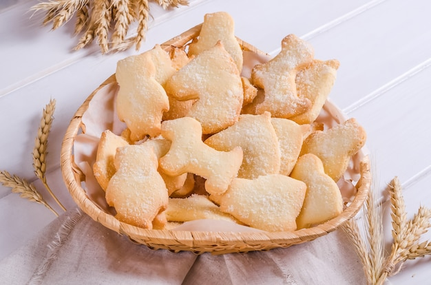 Kruche ciasteczka posypane cukrem w wiklinowym koszu na białym drewnianym tle