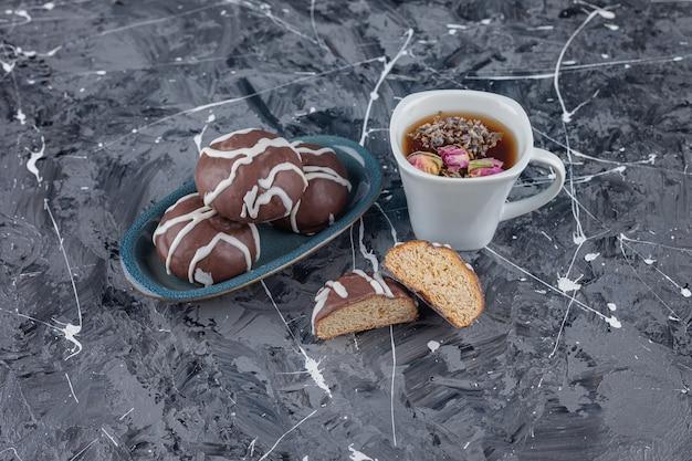 Kruche ciastka oblane białą i ciemną czekoladą ze szklaną filiżanką herbaty.
