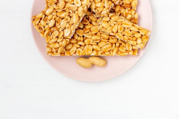 Kruche cukierki orzechowe w karmelu miodowym na talerzu na białym tle