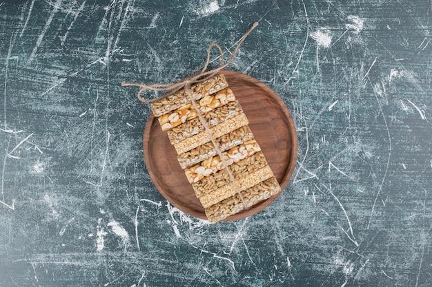 Kruche cukierki związane sznurem na drewnianym talerzu. wysokiej jakości zdjęcie