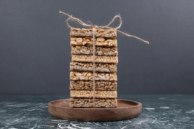 Kruche cukierki związane sznurem na drewnianym talerzu.