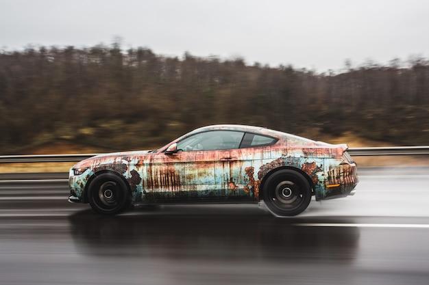 Krwawe tuningowe coupe na drodze w deszczu