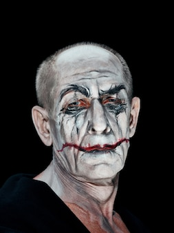 Krwawy motyw halloween: szalona twarz maniaka w dark studio