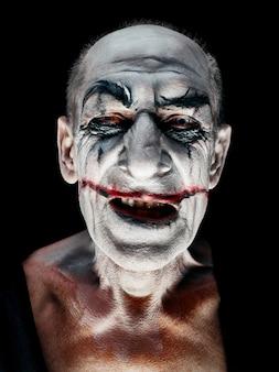 Krwawy motyw halloween: szalona uśmiechnięta twarz maniaka w ciemnym studio