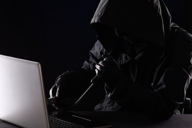Kryminalny haker w kapturze w czarnym ubraniu i kominiarce niszczy laptopa za pomocą narzędzi, śrubokręta i szczypiec na czarnym tle.