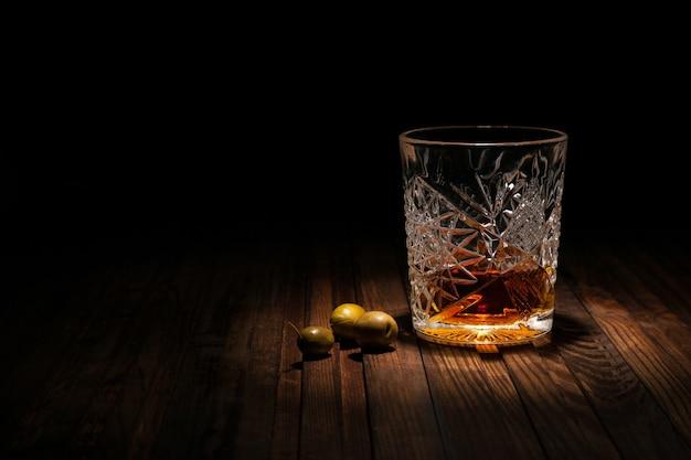 Krystaliczny szkło z whisky i przekąskami na drewnianym stole na czarnym tle