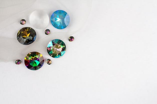 Kryształki kamieni szlachetnych do biżuterii rozrzucone na białym tle