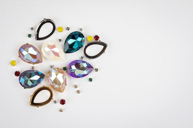 Kryształki kamieni szlachetnych rozrzucone na białym tle