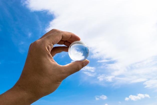 Kryształowa kula lub szklana ziemska piłka. przejrzysta sfera w ręce z jasnym nieba tłem.