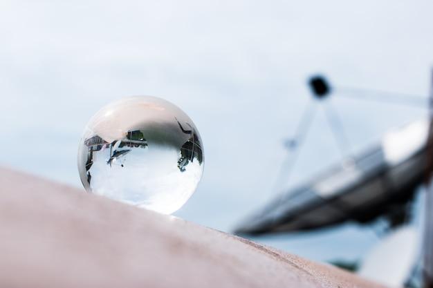 Kryształowa kula lub szklana ziemska piłka. przezroczysta kula z anteną satelitarną.