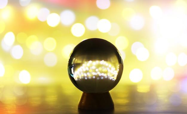 Kryształowa kula na stole z bokeh, światła z tyłu. szklana kula z kolorowym światłem bokeh, koncepcja przewidywania.