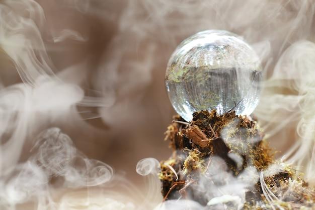 Kryształowa kula w dymie. magiczny dodatek w lesie na pniu. rytualny bal wiedźm i czarowników na starym zgniłym pniu pokrytym mchem.