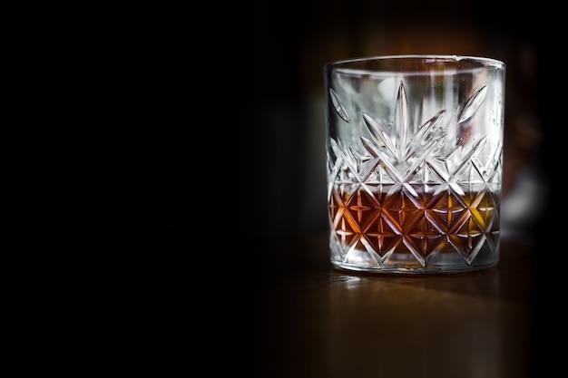 Kryształowa szklanka z whisky, drogi alkohol, czarne tło