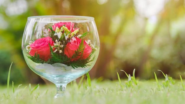 Kryształowe kieliszki do wina są duże ozdobione czerwoną różą na łące pomysły na prezenty dla zakochanych