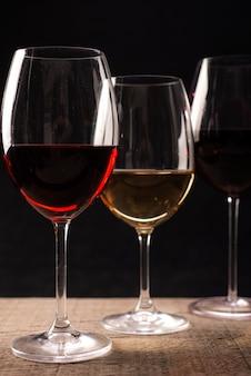 Kryształowe kieliszki z rustykalnym drewnianym stołem do wina czerwonego i białego