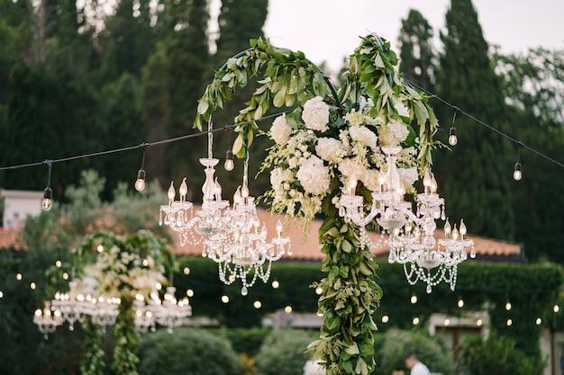 Kryształowe żyrandole i girlandy zdobią kolację weselną na świeżym powietrzu, wśród drzew