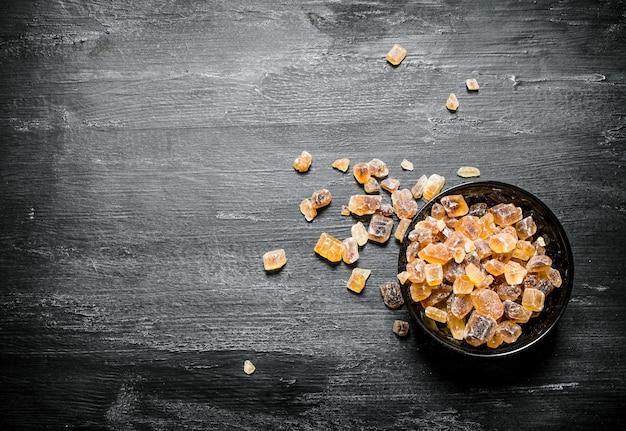 Kryształowy cukier brązowy. na czarnym rustykalnym stole.