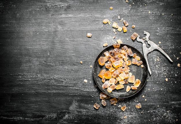 Kryształowy cukier z nożycami do drutu na czarnym rustykalnym stole.