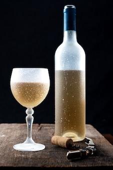Kryształowy kieliszek do białego wina i butelka wina podawana na bardzo zimno, nad rustykalnym drewnianym stołem