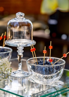 Kryształowy wysoki stojak na ciasto. jagody stoją w szklanym talerzu. niewyraźne tło. ścieśniać.