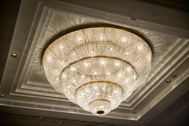 Kryształowy żyrandol świeci zwisając z sufitu w hotelowym holu