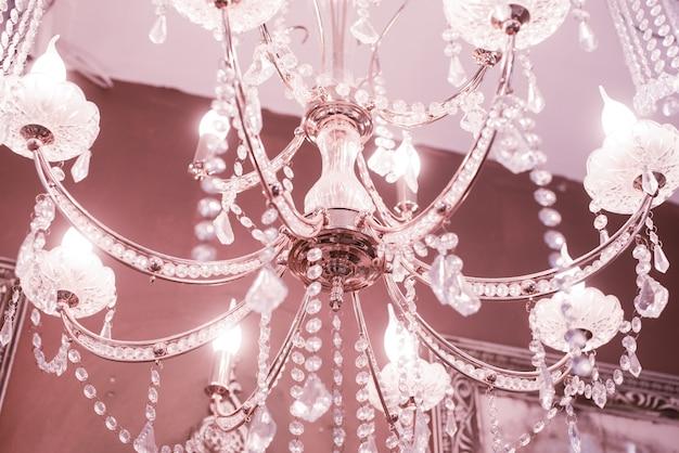Kryształowy żyrandol z bliska. różowe światło. selektywne skupienie.