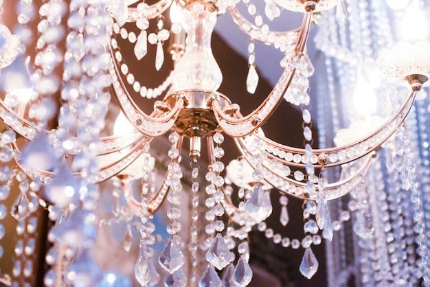 Kryształowy żyrandol z bliska. różowy, fioletowy, srebrny jasny. selektywne skupienie.
