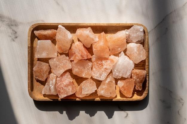 Kryształy różowej soli himalajskiej na drewnianej tacy, deoracja wnętrz, koncepcja spa i opieki zdrowotnej