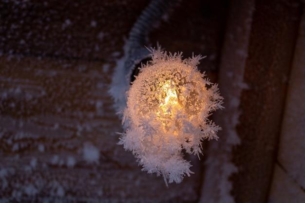 Kryształy śniegu na drewnianej ścianie i żarówka.