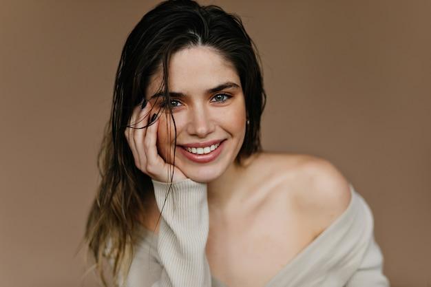 Kryty fotografia fascynującej białej kobiety. modna dziewczyna pozuje ze szczerym uśmiechem.