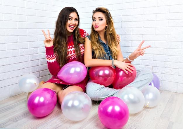 Kryty jasny portret dwóch śmiesznych przyjaciółek, siostry hipster kobiety, szalejący, czas na imprezę, różowy balon, pokazujący naukę, uściski i pocałunki, makijaż, swetry, niesamowity uśmiech.