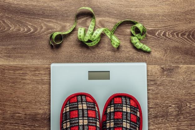 Kryty kapcie na wadze podłogowej i taśmie mierniczej.