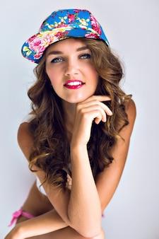 Kryty letni portret młodej, zmysłowej, seksownej sportowej opalonej kobiety pozującej na białej ścianie w kwiecistej czapce i baw się samotnie, jasny makijaż, kręcone włosy.