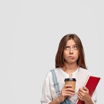 Kryty pionowe ujęcie przyjemnego stylowego nastolatka pozuje na białej ścianie