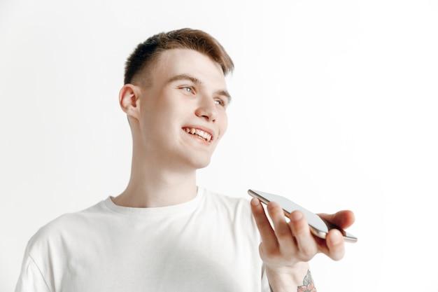 Kryty portret atrakcyjnego młodego mężczyzny na białym tle na szarym tle, trzymając smartfon, używając sterowania głosowego, czując się szczęśliwy i zaskoczony. ludzkie emocje, koncepcja wyrazu twarzy.