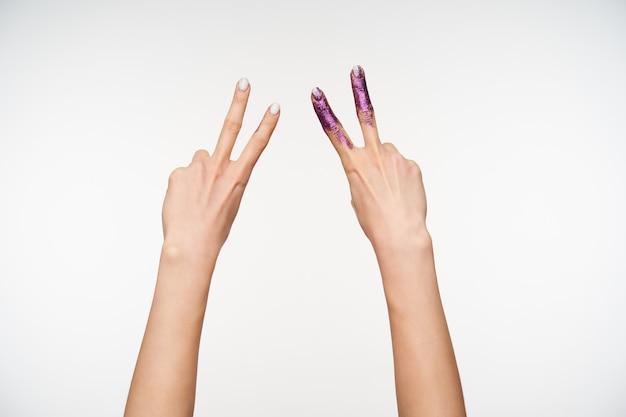 Kryty portret dwóch ładnych kobiecych rąk z białym manicure, tworząc gest zwycięstwa z palcami, będąc na białym tle