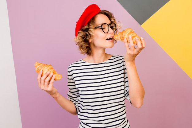 Kryty portret eleganckiej francuskiej kobiety w czerwonym berecie, jedzenie smacznych rogalików.