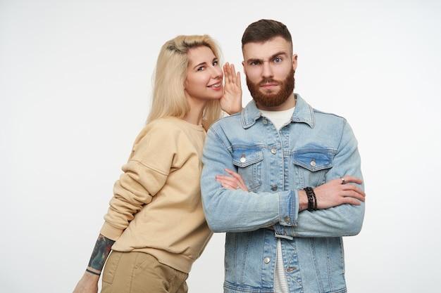 Kryty portret młodego surowego brązowowłosego brodatego mężczyzny marszczącego brwi, podczas gdy jego pozytywna blond ładna dziewczyna mówi mu coś, stojąc na białym