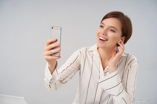 Kryty portret młodej drobnej brązowowłosej kobiety z krótką modną fryzurą trzymającą smartfon w podniesionej dłoni podczas rozmowy wideo, uśmiechając się szeroko podczas pozowania na biało