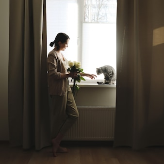 Kryty portret młodej kobiety bawiącej się kotem w domu