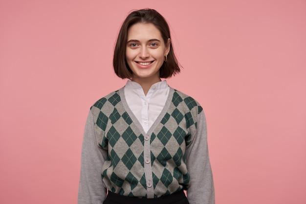 Kryty portret młodej kobiety brunetka, nosi niedbale z uśmiechem na różowo.