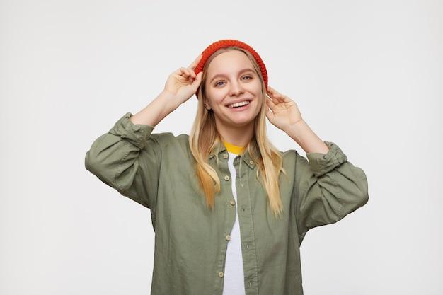 Kryty portret młodej uroczej blondynki o długich włosach z naturalnym makijażem, wyglądająca pozytywnie i podnosząca ręce do głowy, odizolowana na niebiesko